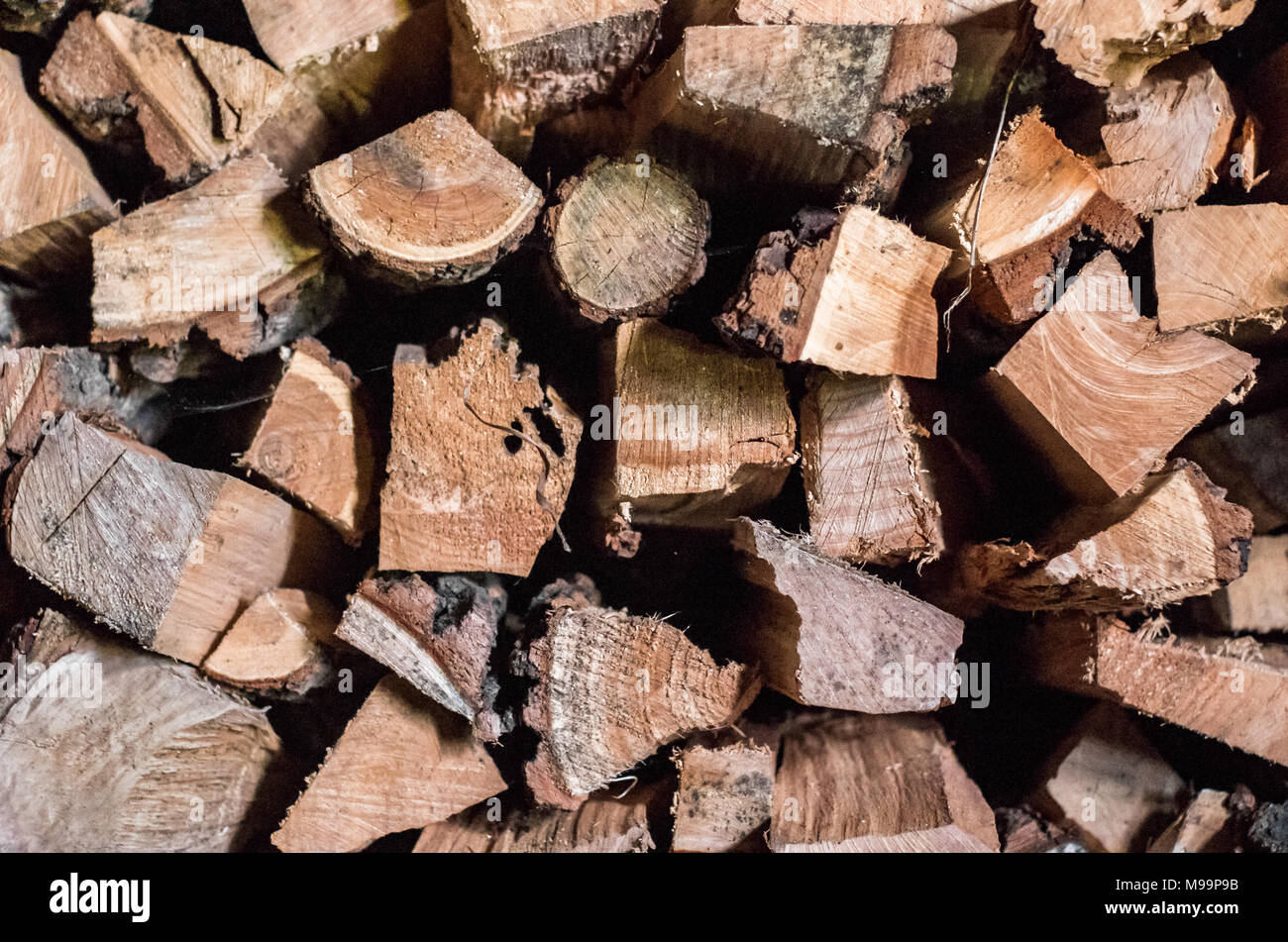 Preparing for winter and making cold season warmer concept: stack of firewood as a graphic resource for natural background - Stock Image