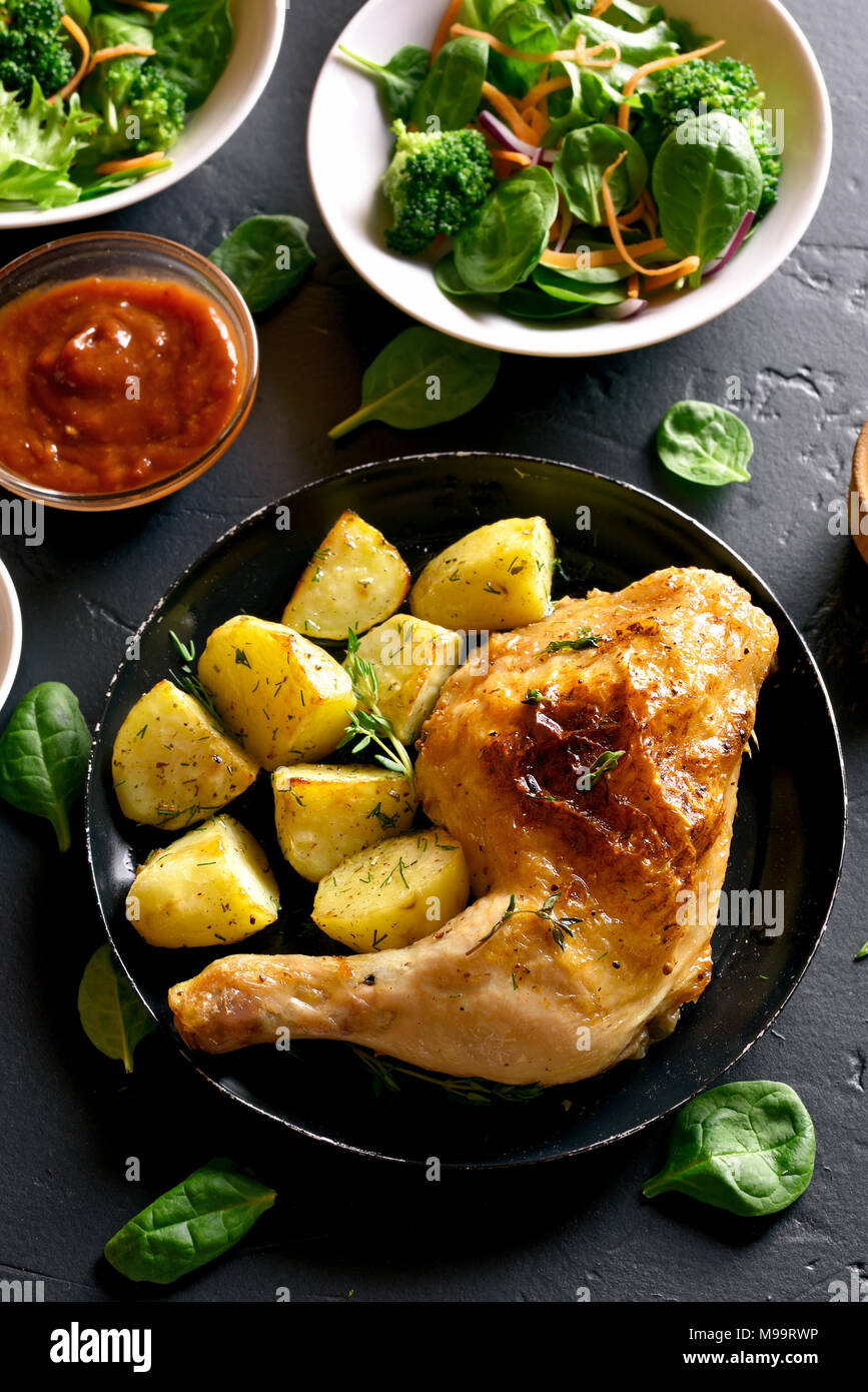Roasted chicken leg with potato. Dish for dinner. Top view - Stock Image