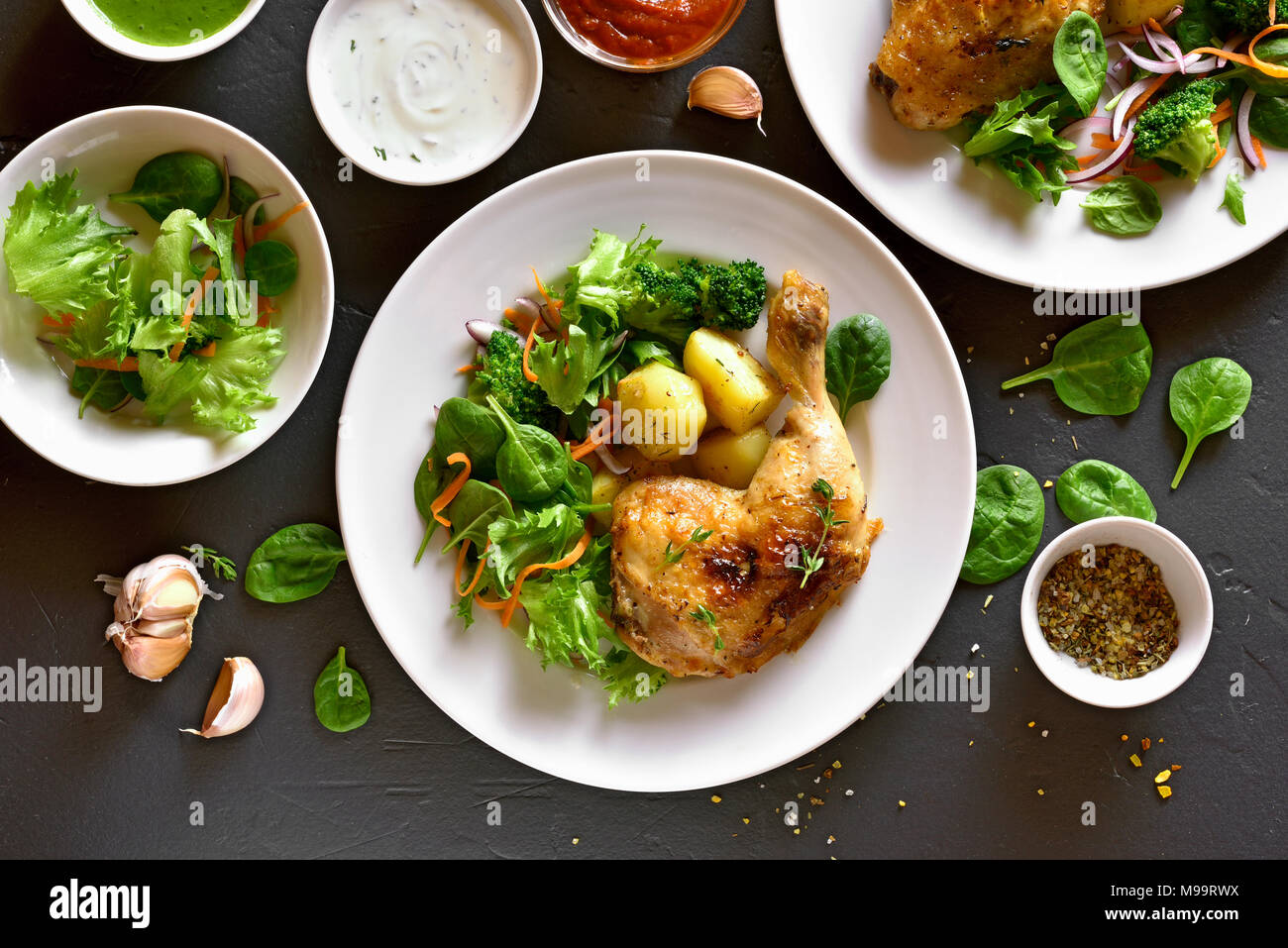 Tasty baked chicken leg with potato and green salad. Dish for dinner. Top view, flat lay - Stock Image