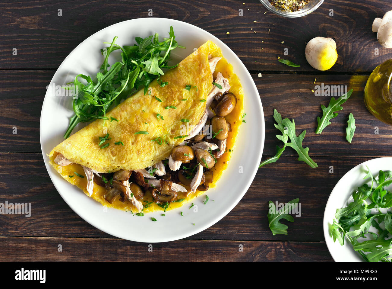 Omelet with mushrooms, chicken meat, greens on wooden table. Healthy food for breakfast. Top view, flat lay - Stock Image