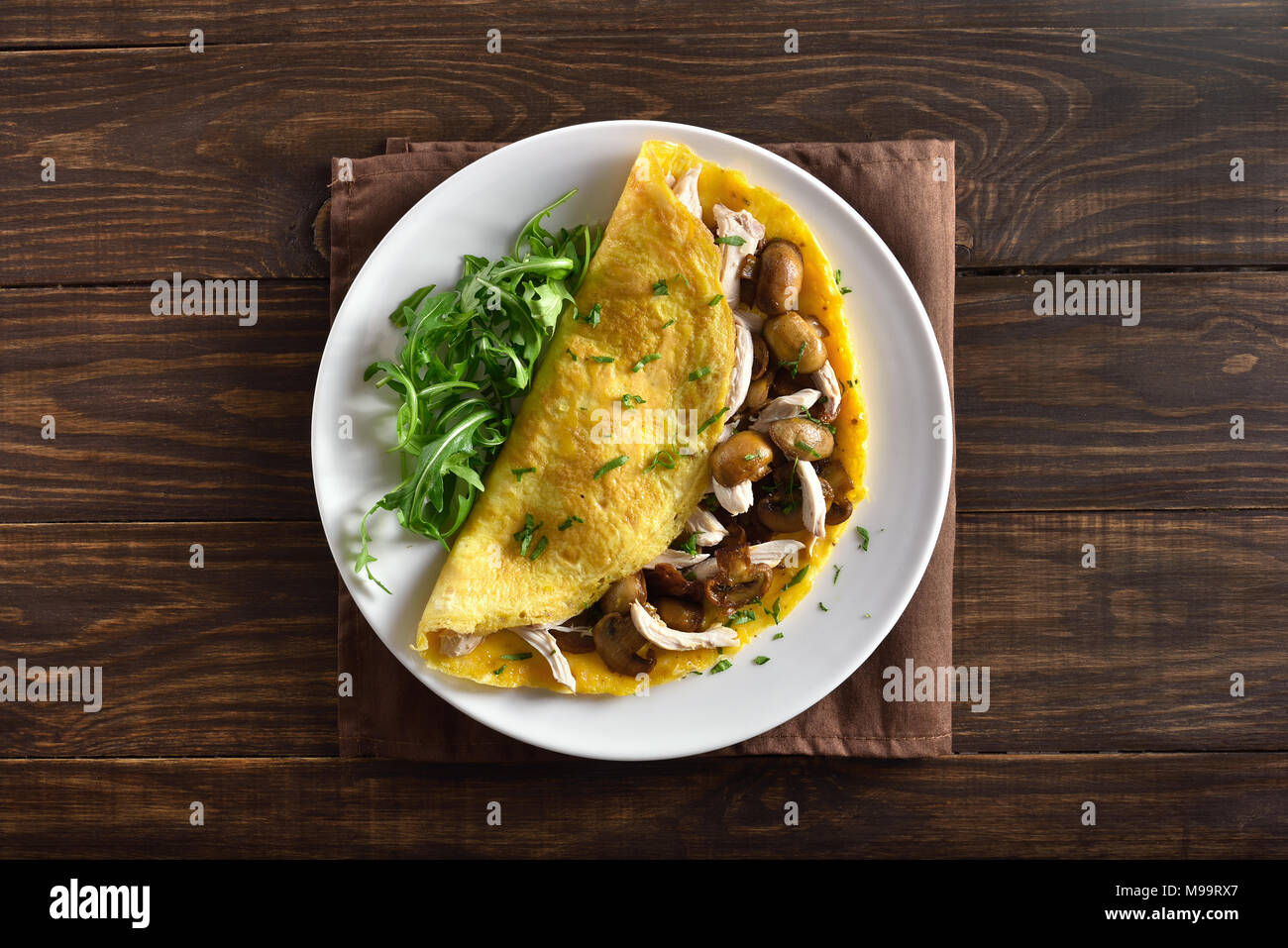Healthy food for breakfast. Omelette stuffed with mushrooms, pieces of chicken meat, greens on wooden table. Top view, flat lay - Stock Image