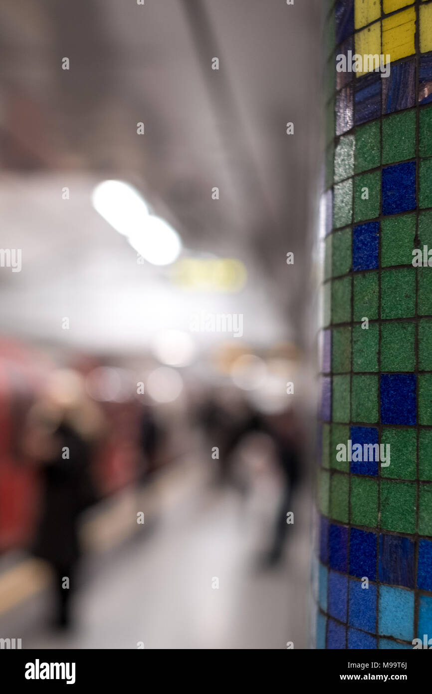 Train platform at Tottenham Court Road underground station showing blurred commuters walking, train in background and mosaic tiles by Eduardo Paolozzi - Stock Image