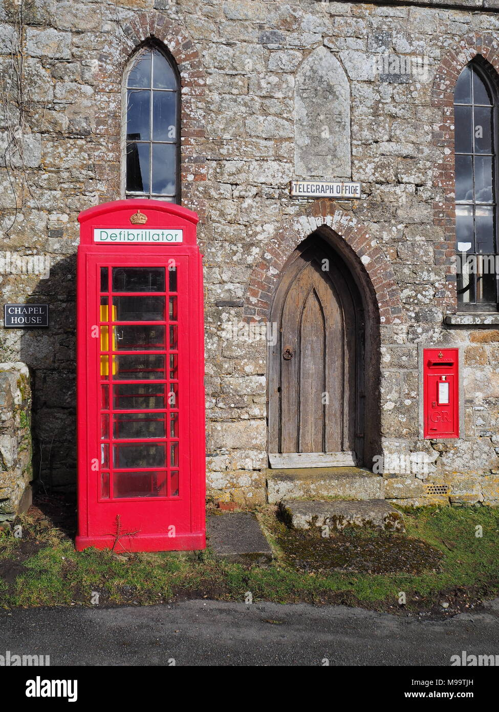 Traditional red British public telephone box containing a defibrillator unit, Dartmoor - Stock Image