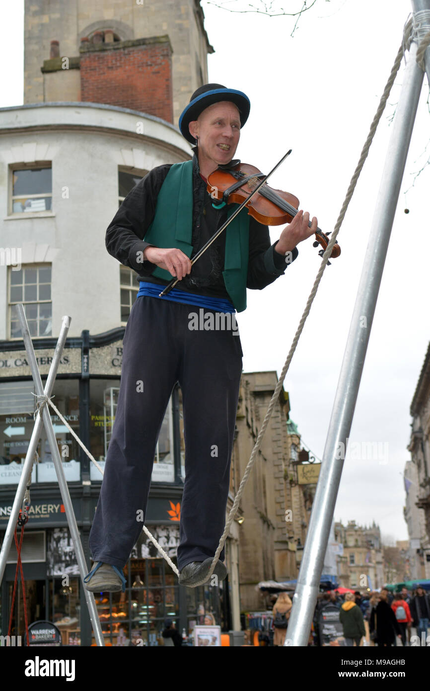 Bristol, UK. 24th March 2018. An afternoon of street entertainment in  Wine Street, Bristol. A performance of Slacklining between two post by by person playing a violin and skillfully balancing while walking on a rope suspended in midair and watched by spectators .Robert Timoney/Alamy/live/News - Stock Image