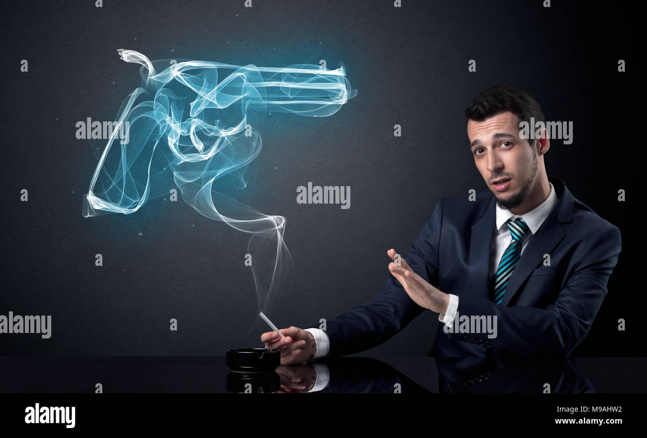 Businessman resting and smoking in a dark room. - Stock Image