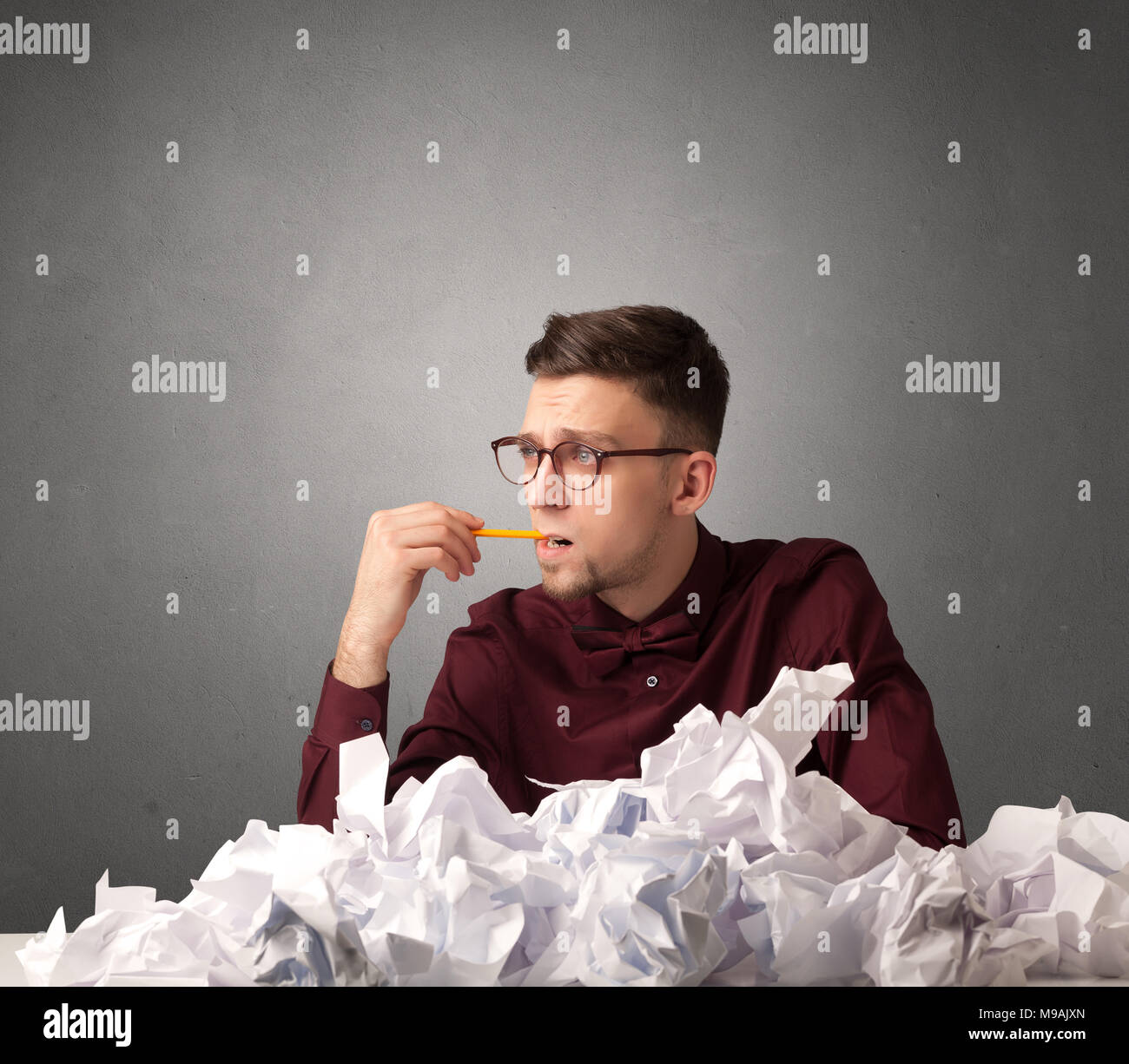 Young businessman sitting behind crumpled paper with grey background  - Stock Image