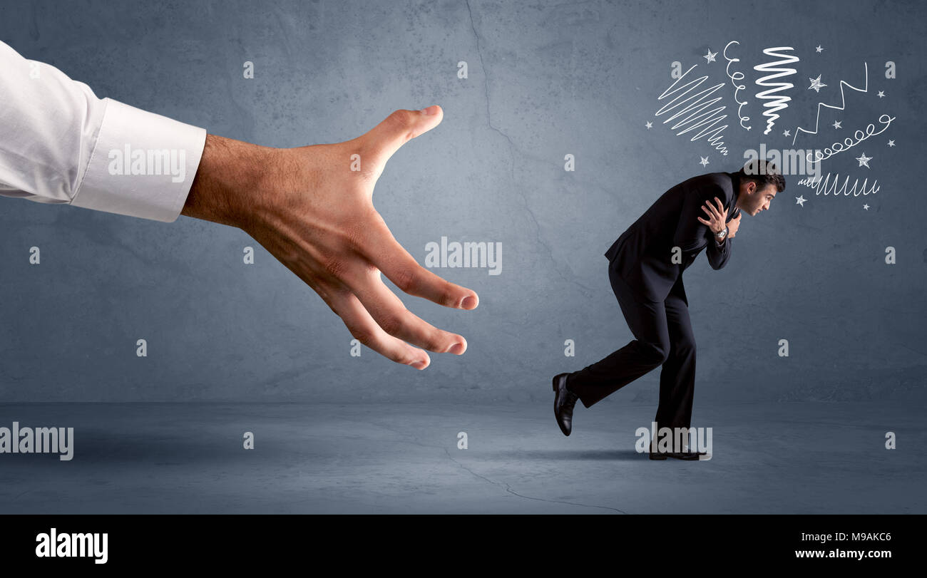 Stressful businessman running from a big hand concept on background - Stock Image