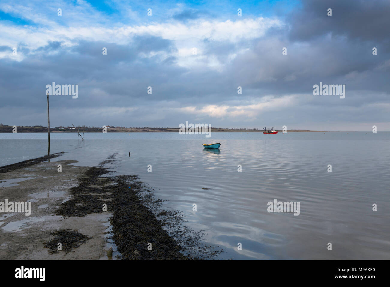 Looking across the Swale from the slipway towards the Isle of Sheppey & two small boats from Kent Wildlife Trust's Oare Marshes, Faversham, Kent, UK. Stock Photo