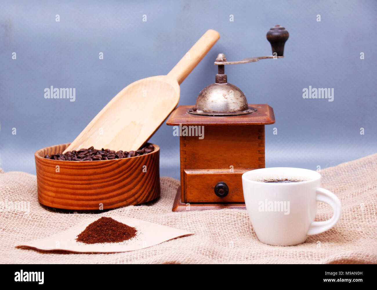 A picture of a cup of coffee, grinder and a coffee filter - Stock Image