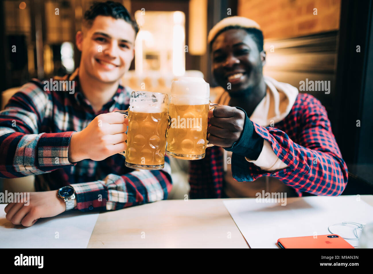 Two best friends or college mates having beer in pub. Afro American man talking to his Caucasian friend, looking at camera - Stock Image