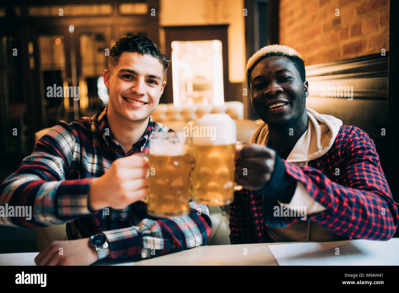 Close up of a two happy male friends drinking beer at pub - Stock Image