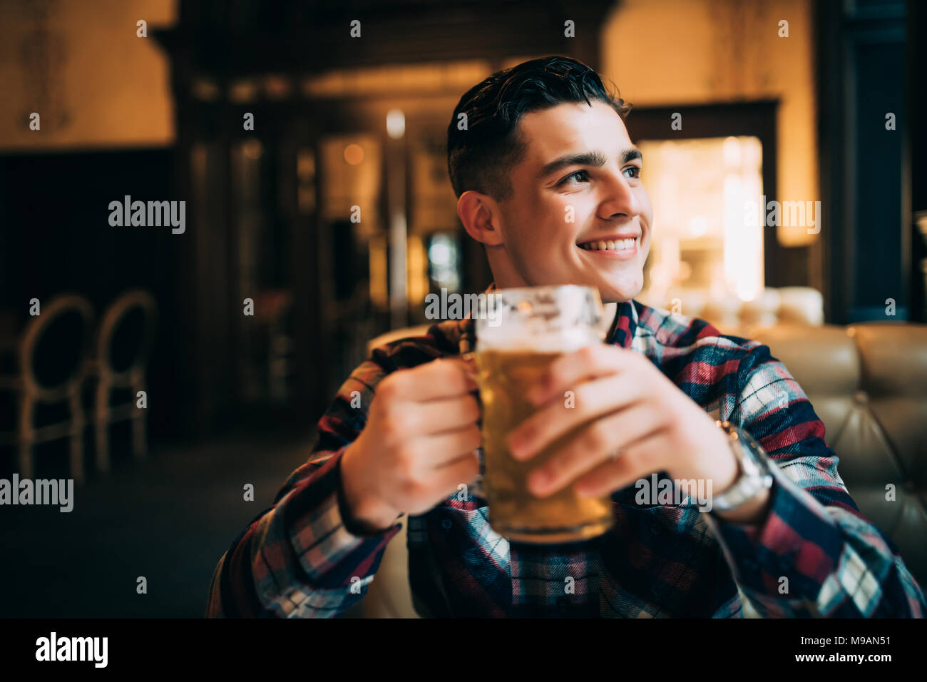 A young man with a beer in a bar - Stock Image