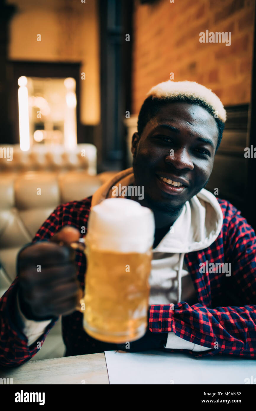 Happy handsome african american young man drinking beer - Stock Image