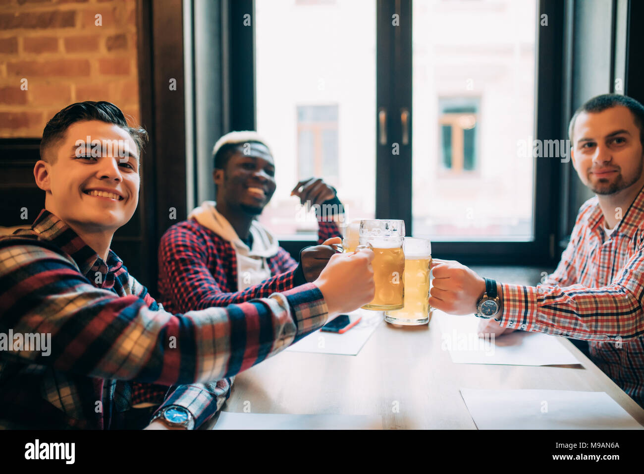 Group of happy young office workers clinking with beer at pub, looking at each other, smiling. - Stock Image