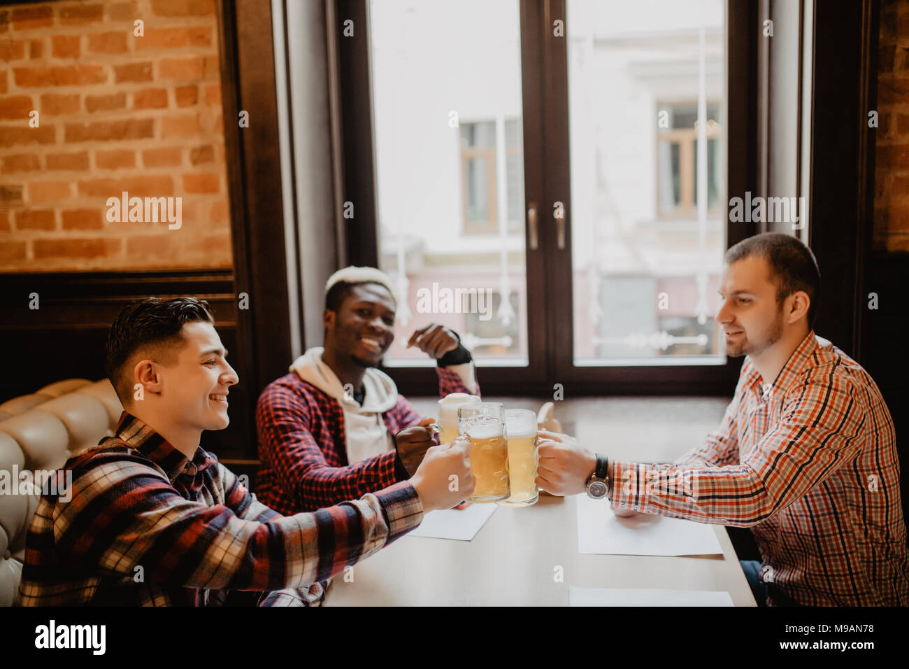 Handsome guys are clinking bottles of beer, looking at camera and smiling while resting in pub - Stock Image