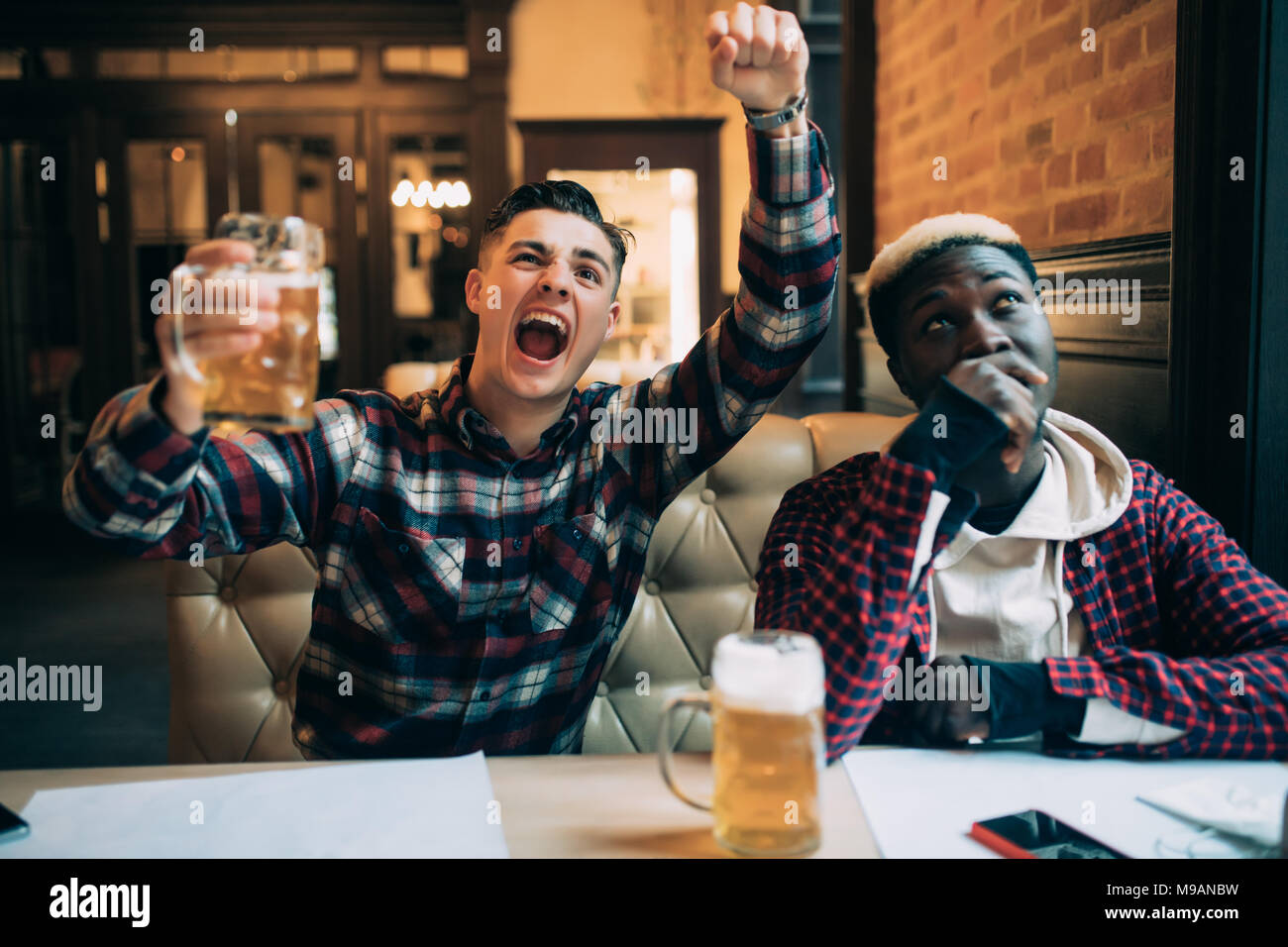 Handsome young man holding his beer and happy shouting looking at the TV screen watching football game with his upset afro american friends at the loc - Stock Image
