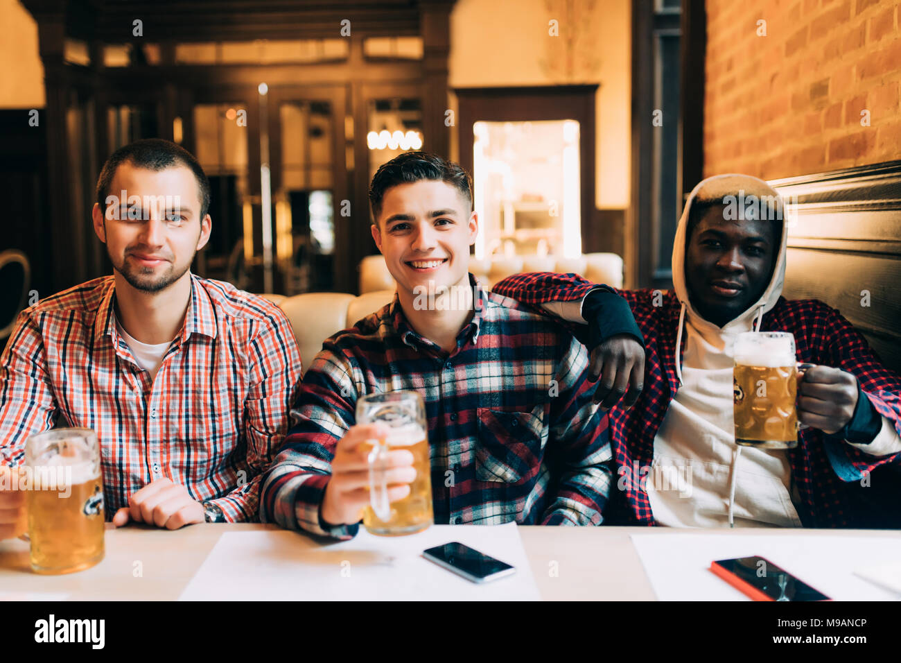Meeting with the best friends. Three happy young men in casual wear talking and drinking beer while sitting in bar Stock Photo