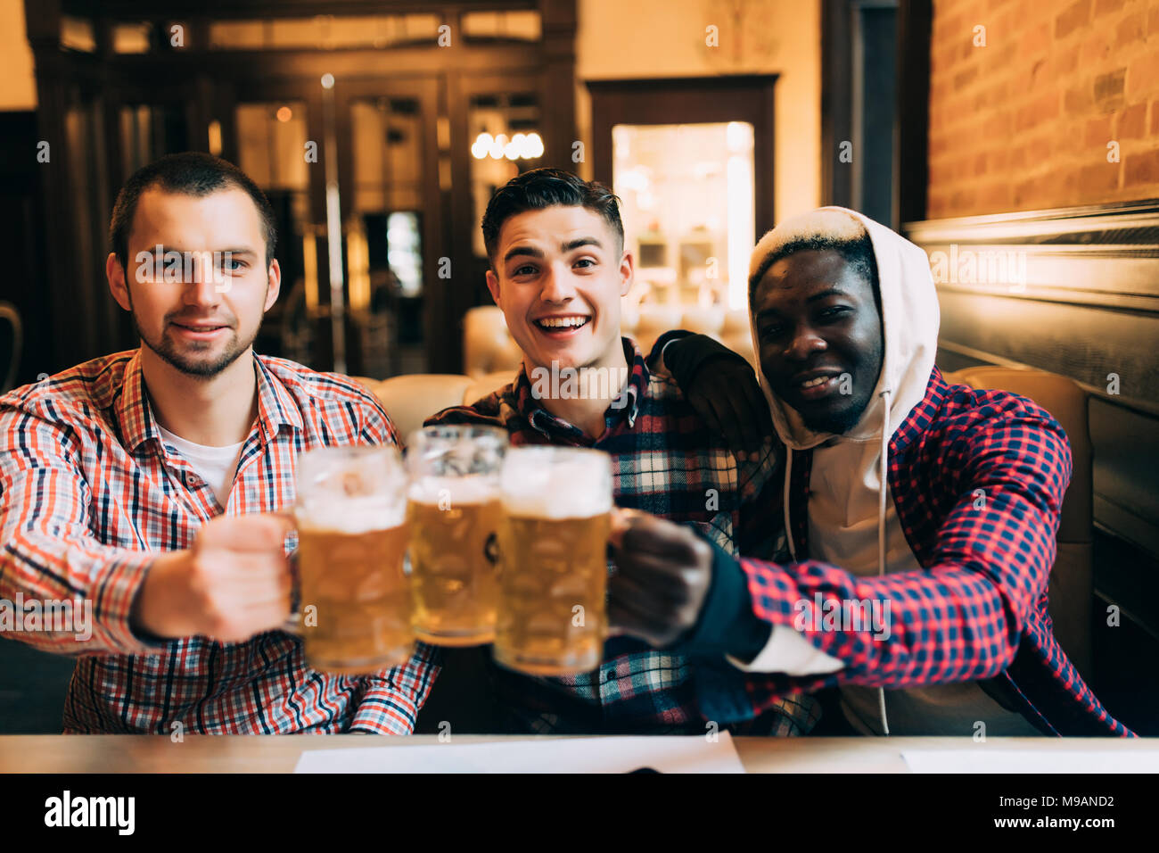 Happy male friends drinking beer and clinking glasses at bar or pub - Stock Image