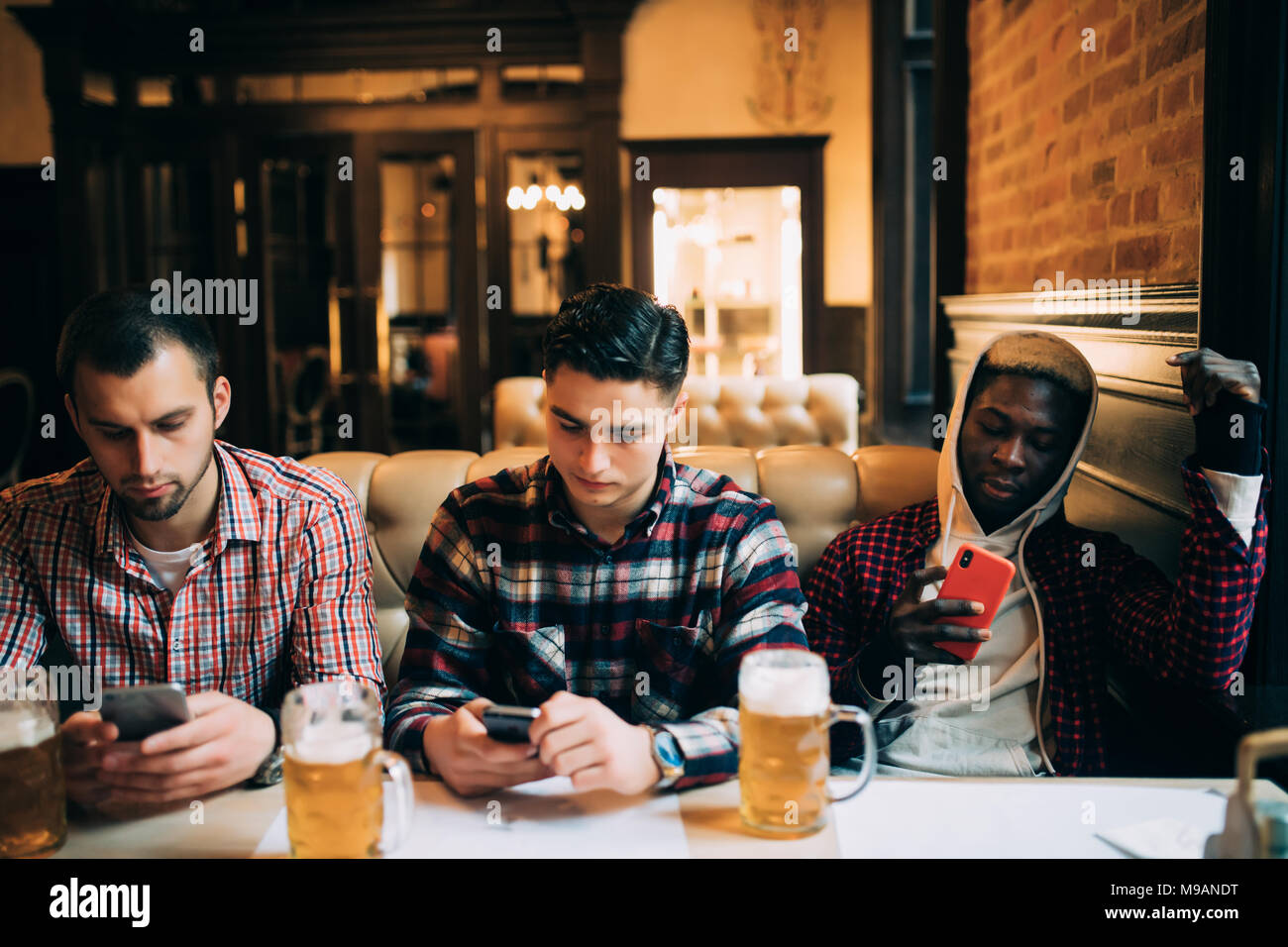 people, men, leisure, friendship and technology concept - male friends with smartphones drinking beer at bar or pub - Stock Image