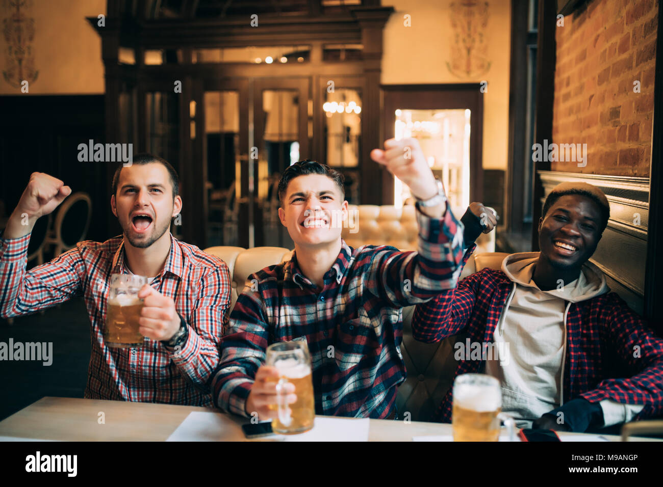 Happy football fans or male friends drinking beer and celebrating victory at bar or pub - Stock Image