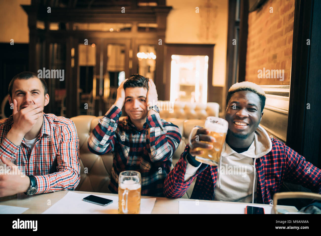 Watching TV in bar. Two happy young men drinking beer and gesturing while sitting in bar - Stock Image