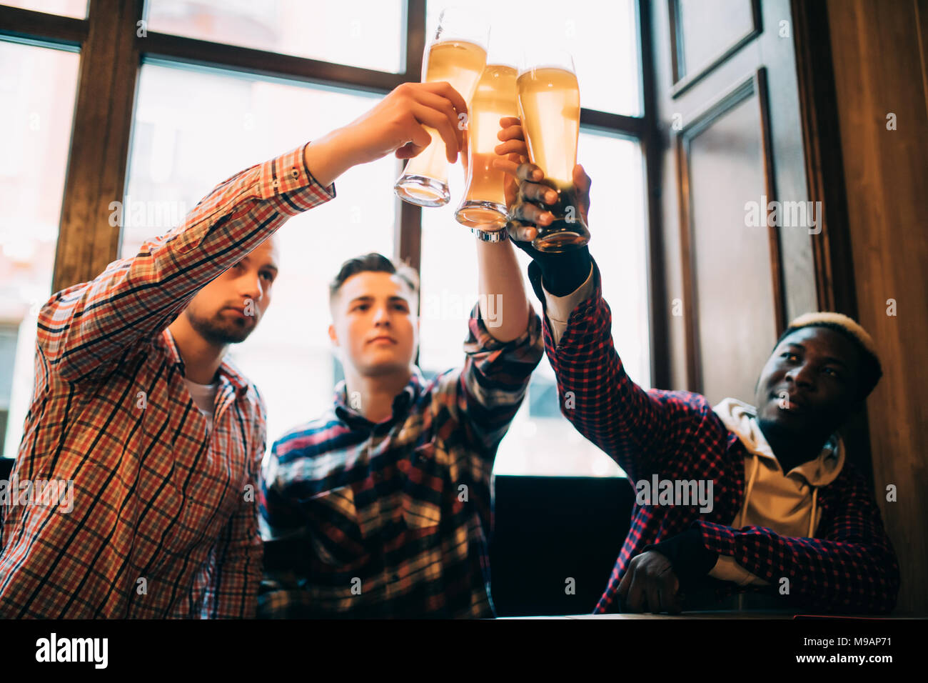 Multiracial friends men cheers with beer in glasses in pub. - Stock Image
