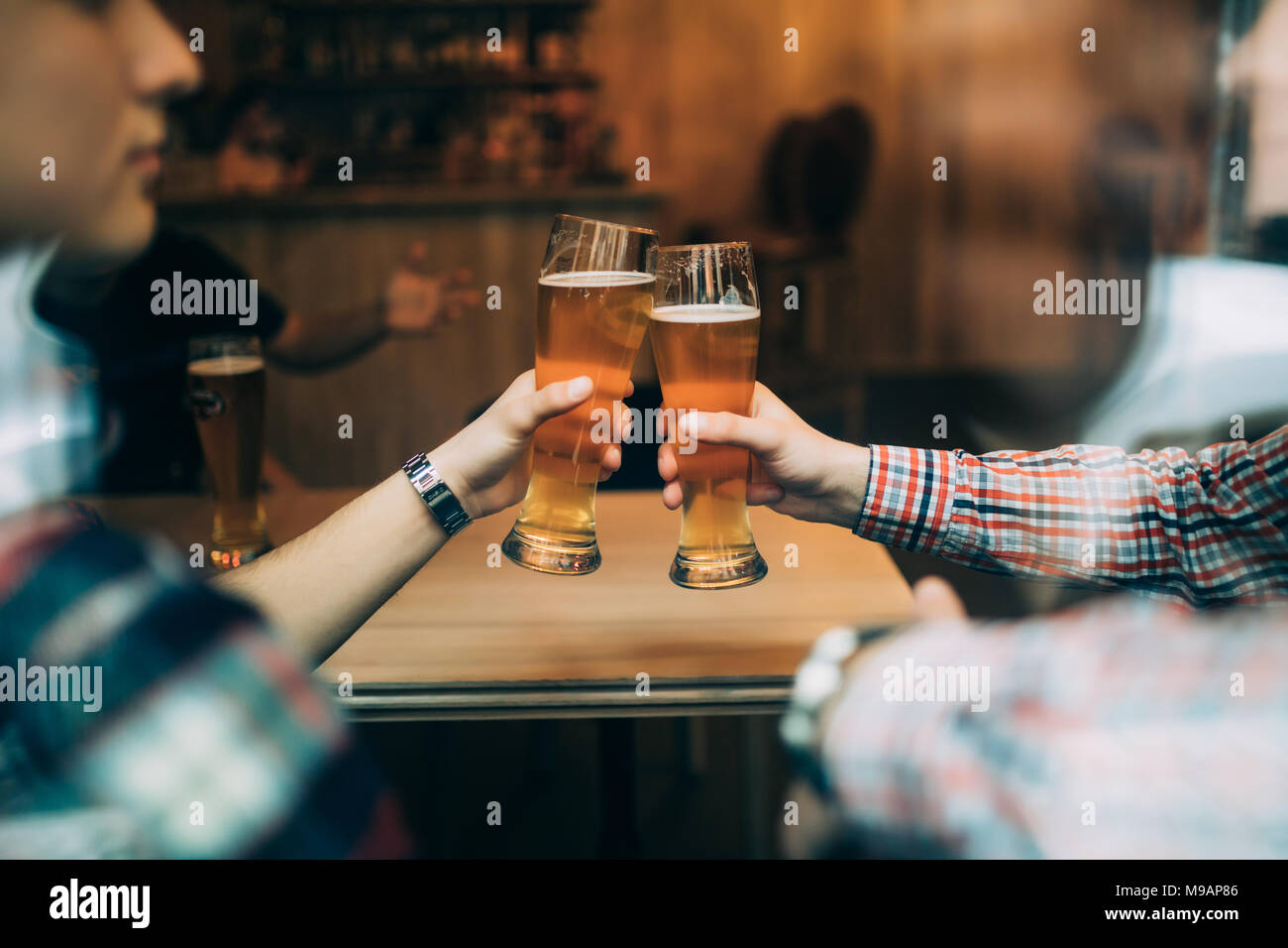 Close up friends sitting at the pub cheers with beers glasses trough window. - Stock Image