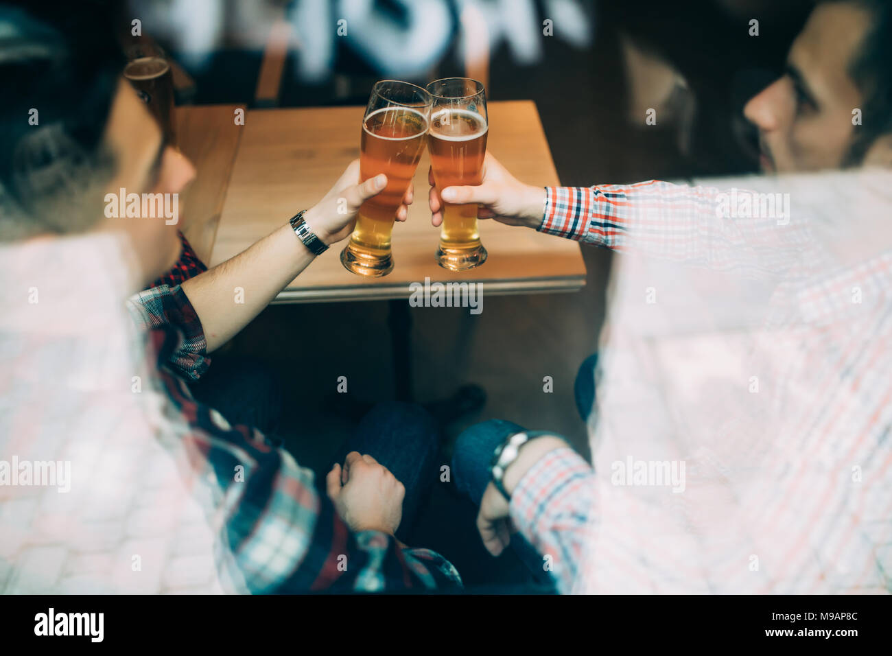 Multiracial old friends meet in pub and drink beer, talking and have fun view through window. Stock Photo