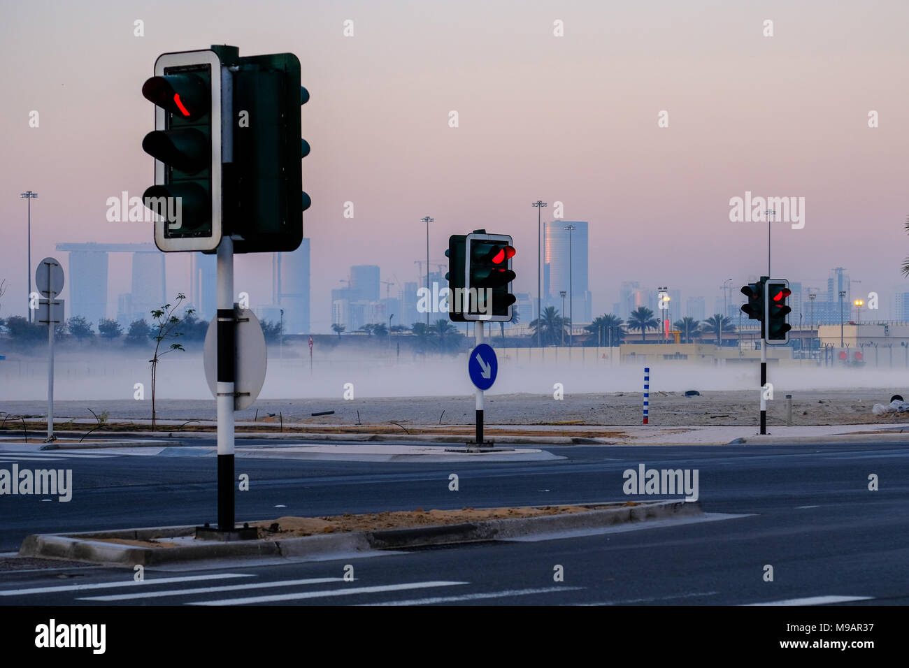 Traffic light posts, captured in a mysty morning with City buildings in a distance, Abu Dhabi, UAE. - Stock Image