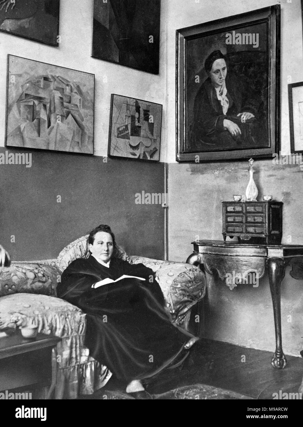Gertrude Stein (1874-1946). Portrait of the American novelist and playwright sitting in her Paris studio with a painting of her by Picasso on the wall, c.1930. - Stock Image