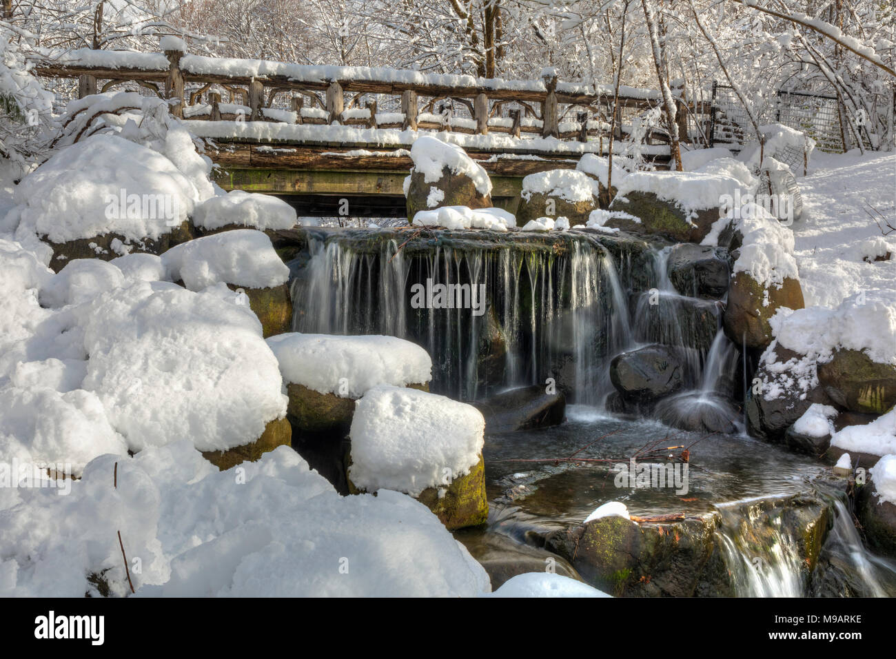 Snowclad Binnen Bridge above silky Binen falls after a Spring snowfall in Prospect Park, Brooklyn, New York. Stock Photo