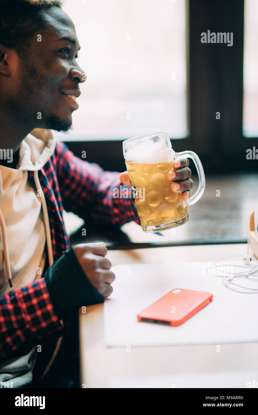 Handsome Afro American is drinking beer while resting in pub - Stock Image