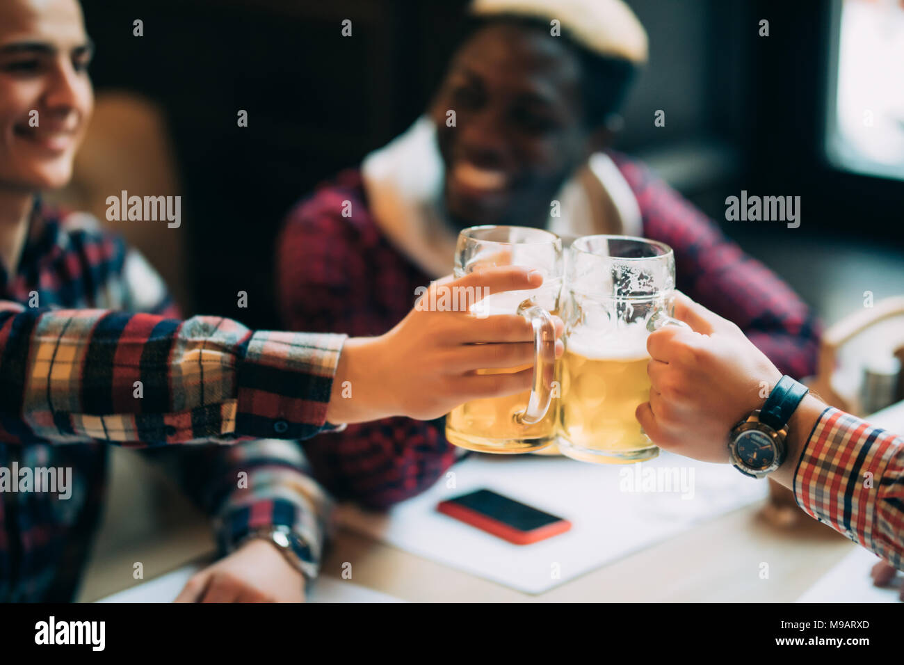 Happy smiling male friends clinking with beer mugs in pub - Stock Image