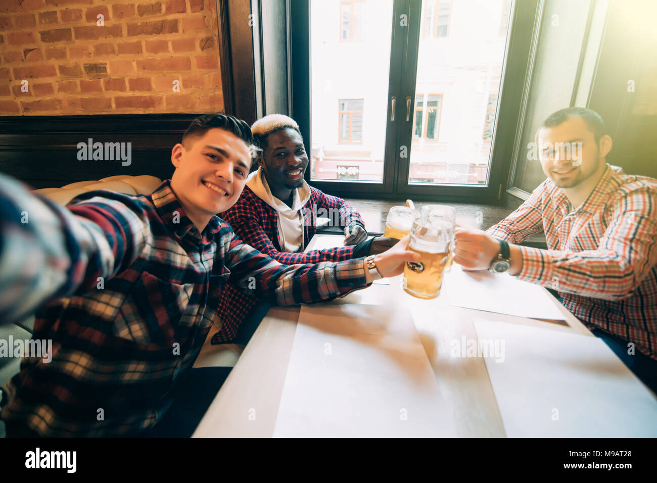 people, leisure, friendship, technology and bachelor party concept - happy male friends taking selfie and drinking beer at bar or pub - Stock Image