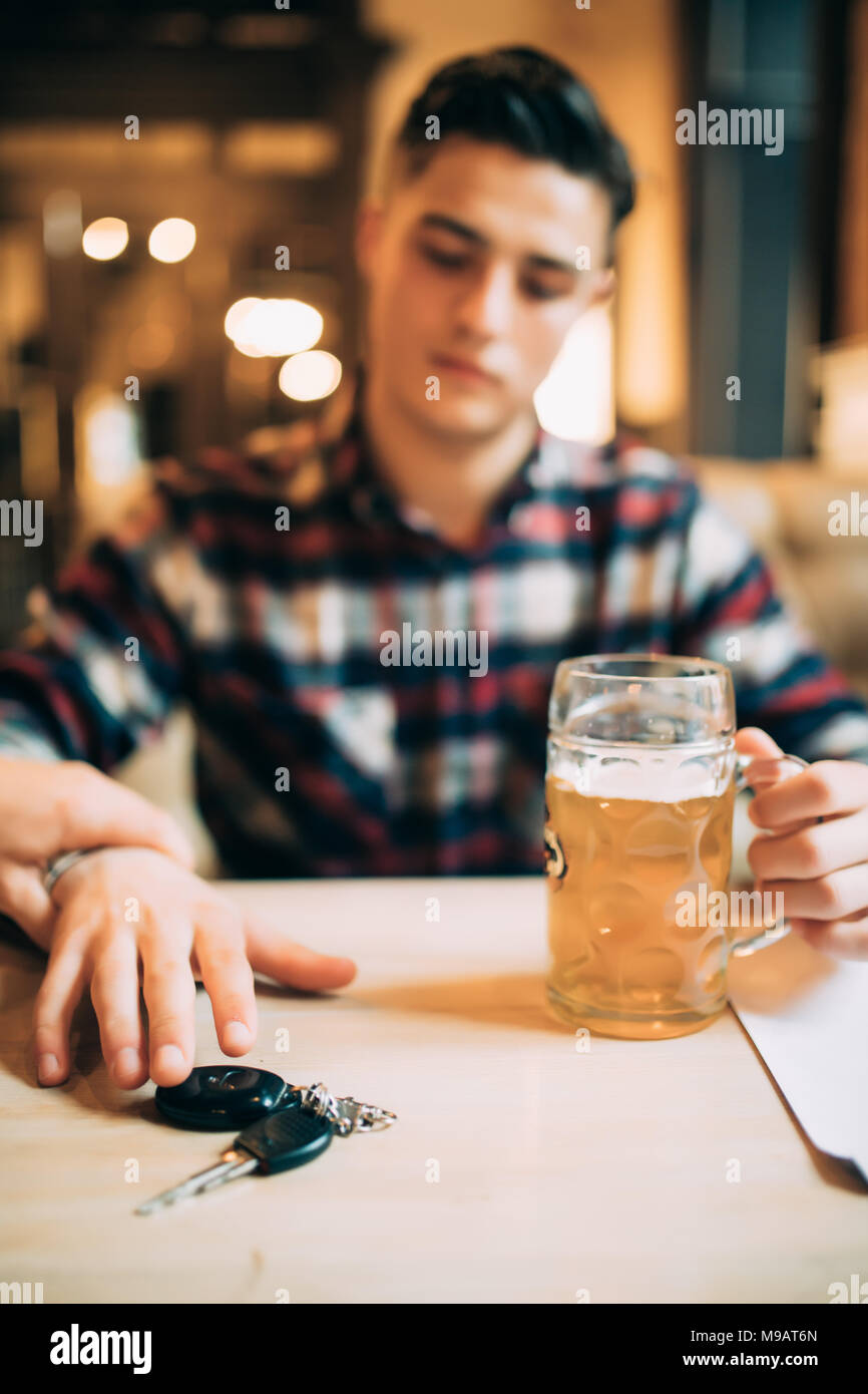Cropped image of drunk man talking car keys and his friend stopping him - Stock Image
