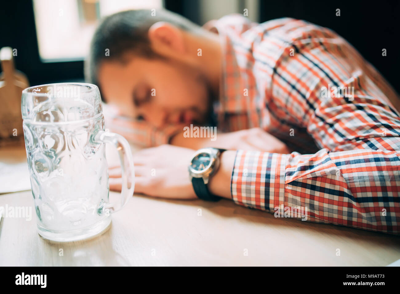 Drunk male customer leaning at the bar counter and sleeping while glass with beer standing near him - Stock Image