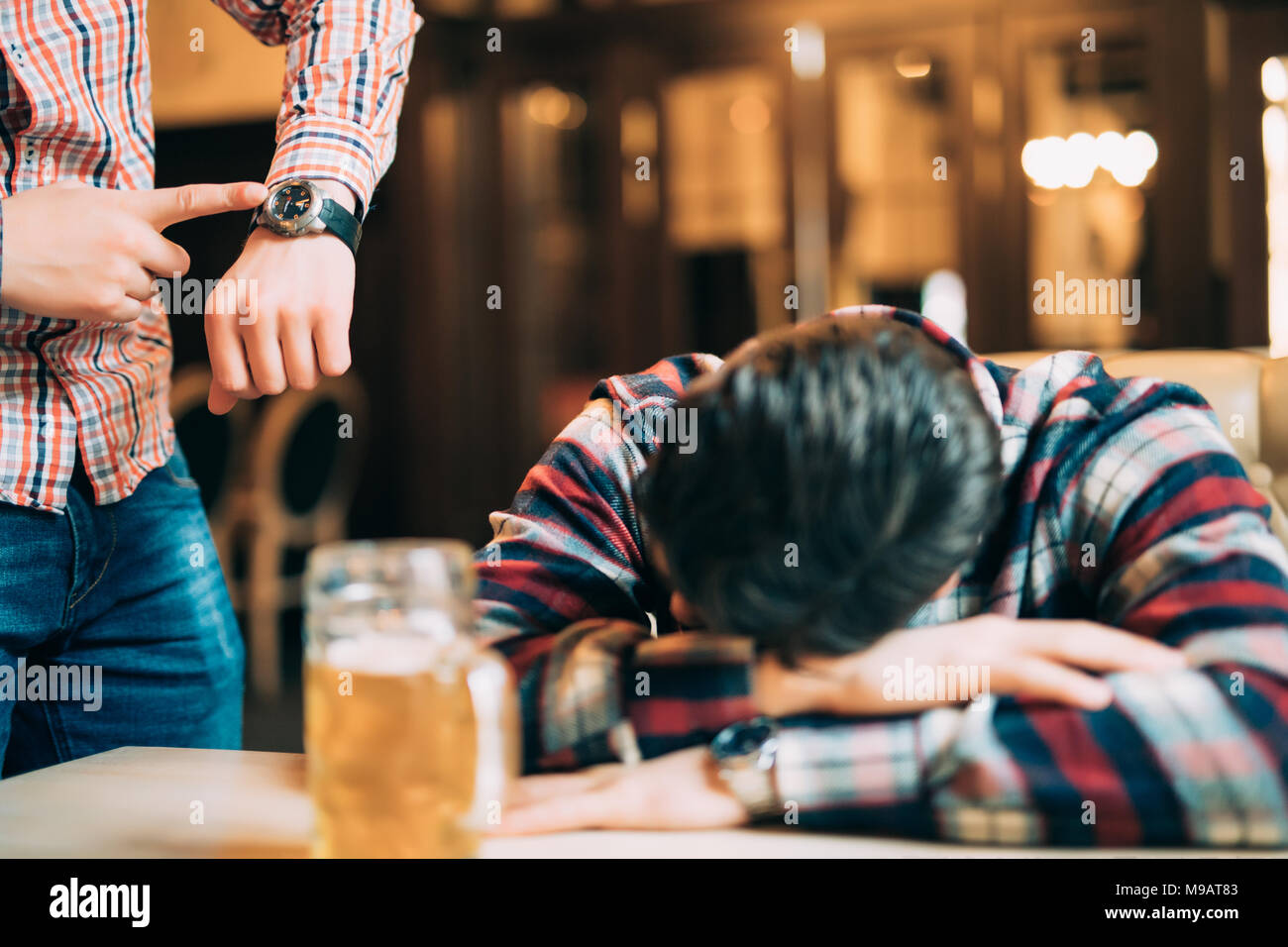 Young man in casual clothes is sleeping near the mug of beer on a table in pub, another man is waking him up. - Stock Image