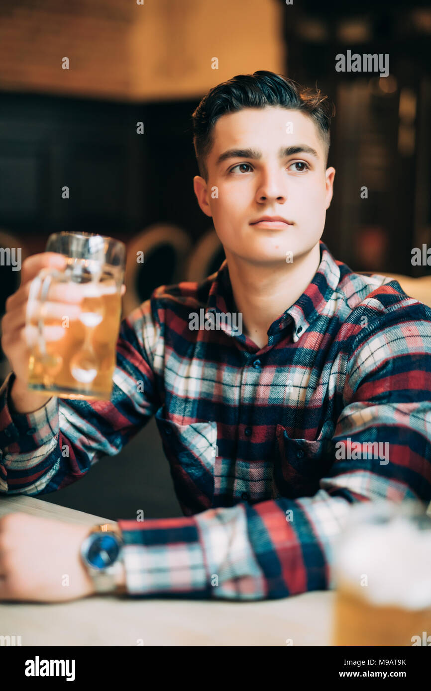 Man in beer pub. Cheerful young man holding a beer mug and smiling while sitting in bar - Stock Image