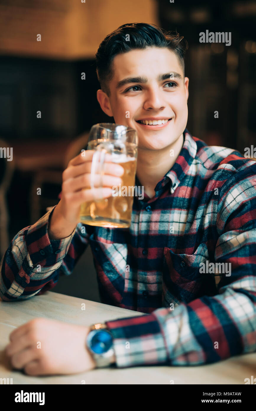 Young man sitting at bar counter with a pint of light beer - Stock Image