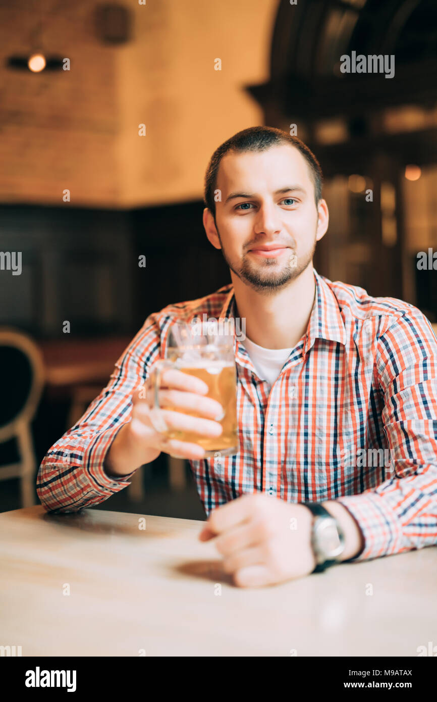 Handsome young man drinking light beer in a pub - Stock Image