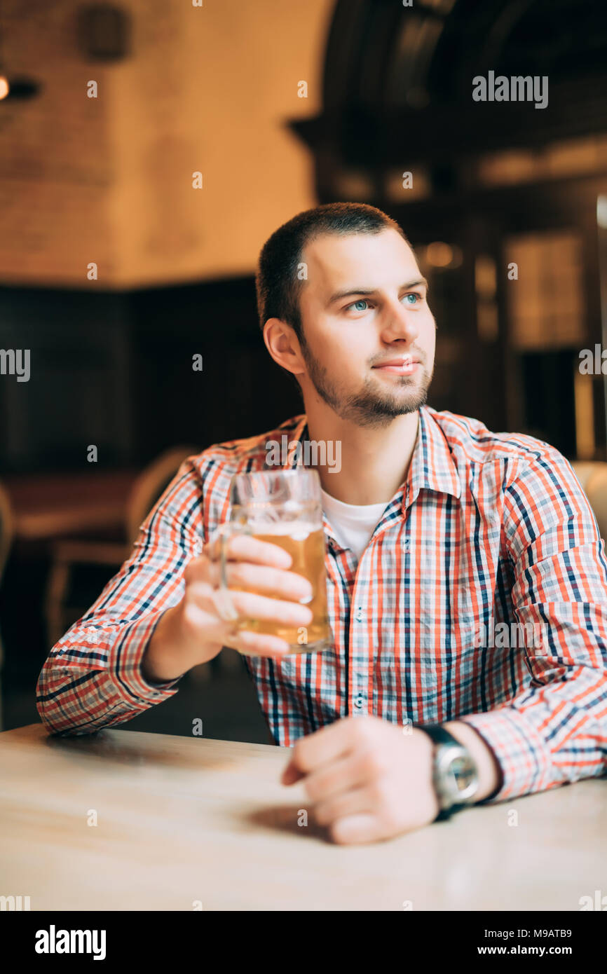 Handsome young man drinking light beer in a pub. - Stock Image