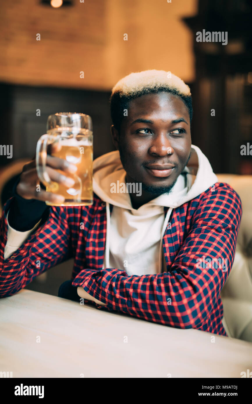 African American man with drink at bar - Stock Image
