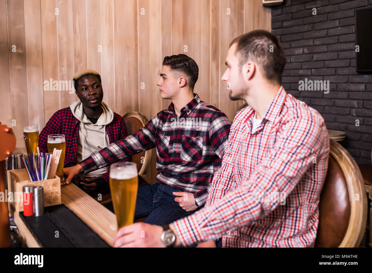 Friends met after a hard day. Three cheerful friend clink beer at the bar and drink a beer. - Stock Image