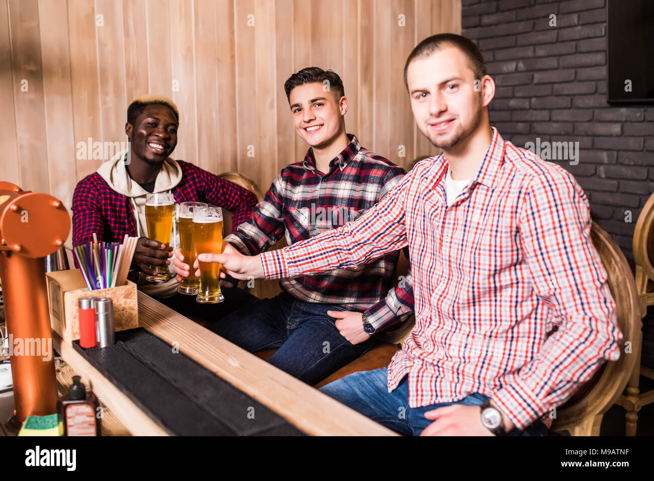 Cheerful old friends having fun and drinking draft beer at bar counter in pub. Stock Photo