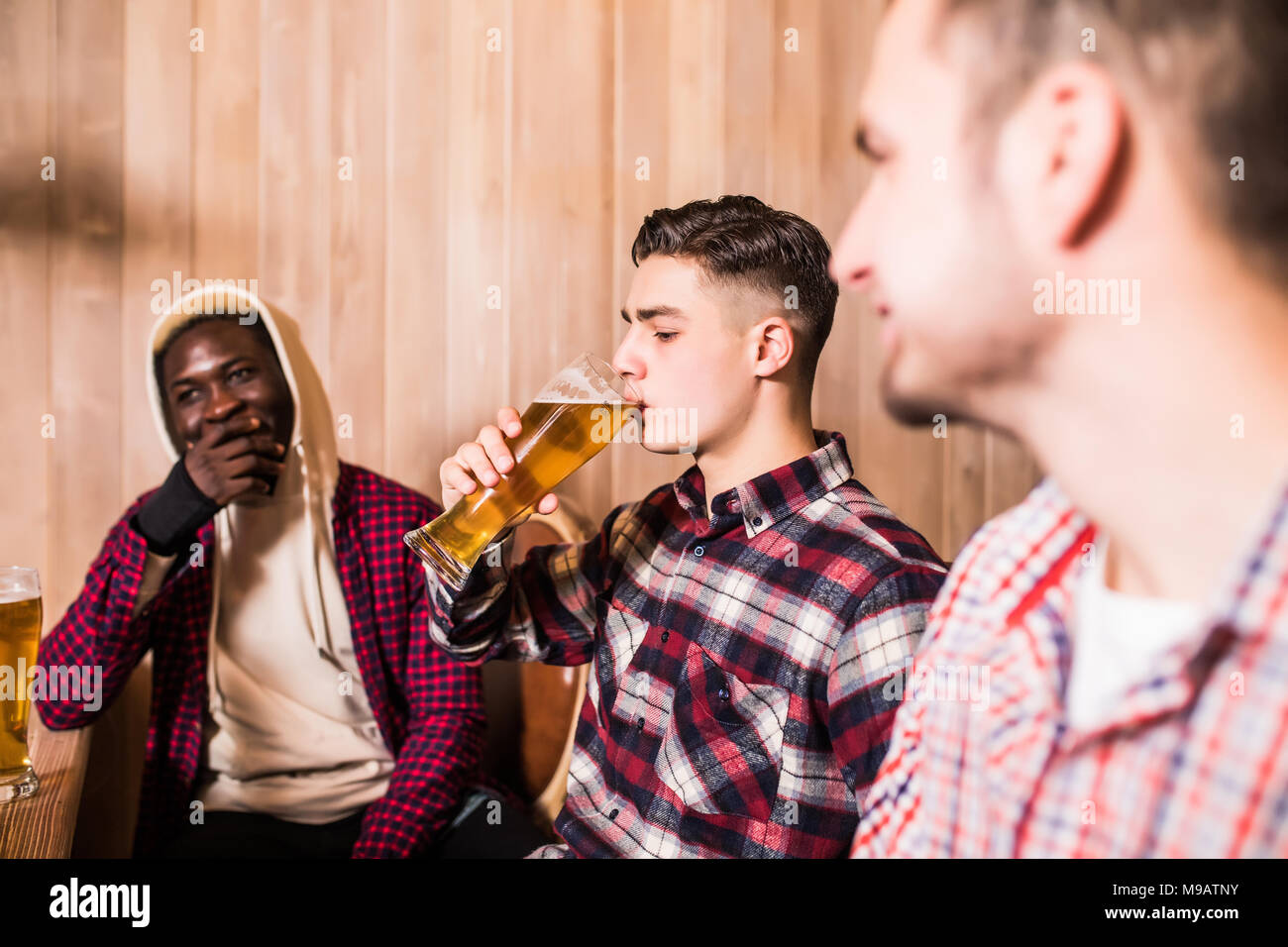 Three young men in casual clothes are smiling drinking beer while sitting at bar counter in pub - Stock Image
