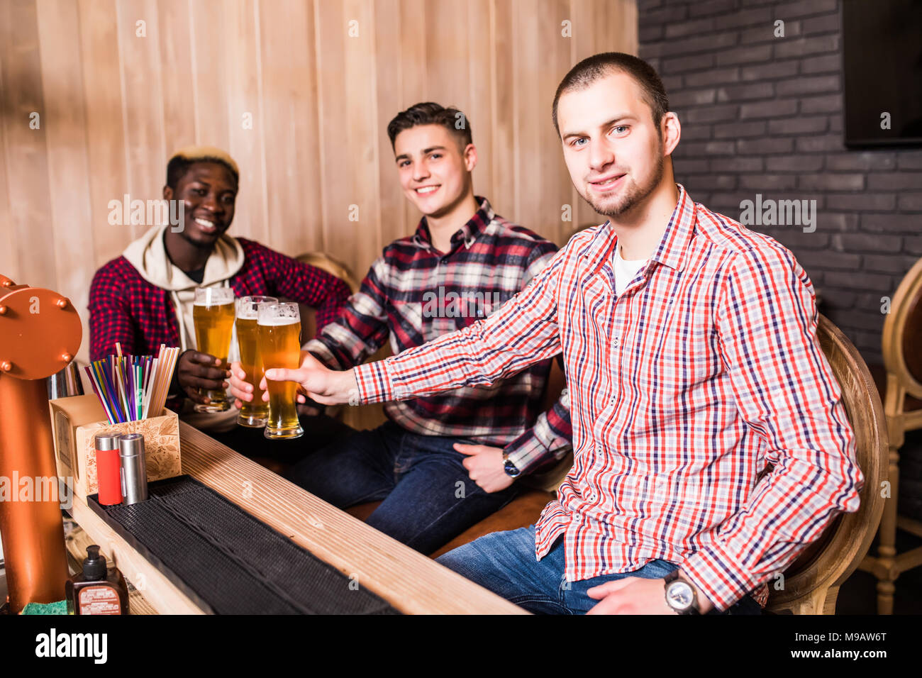 Cheerful old friends having fun and drinking draft beer at bar counter in pub. - Stock Image