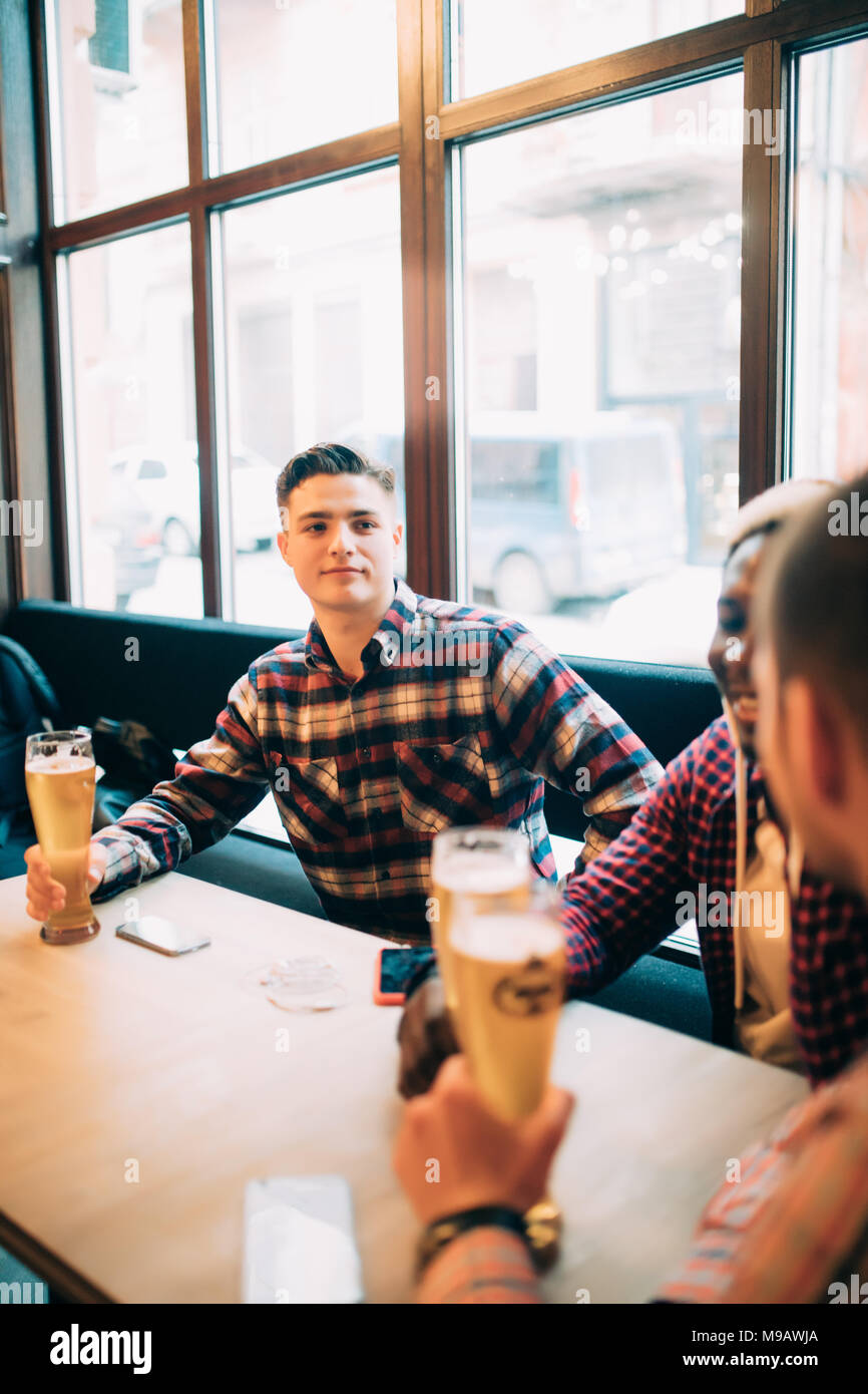 people, men, leisure, friendship and celebration concept - happy male friends drinking beer and clinking glasses at bar or pub - Stock Image