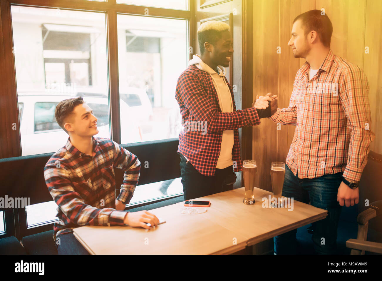 Happy to finally meet old male friends in bar. Shaking hands and smiling. Stock Photo