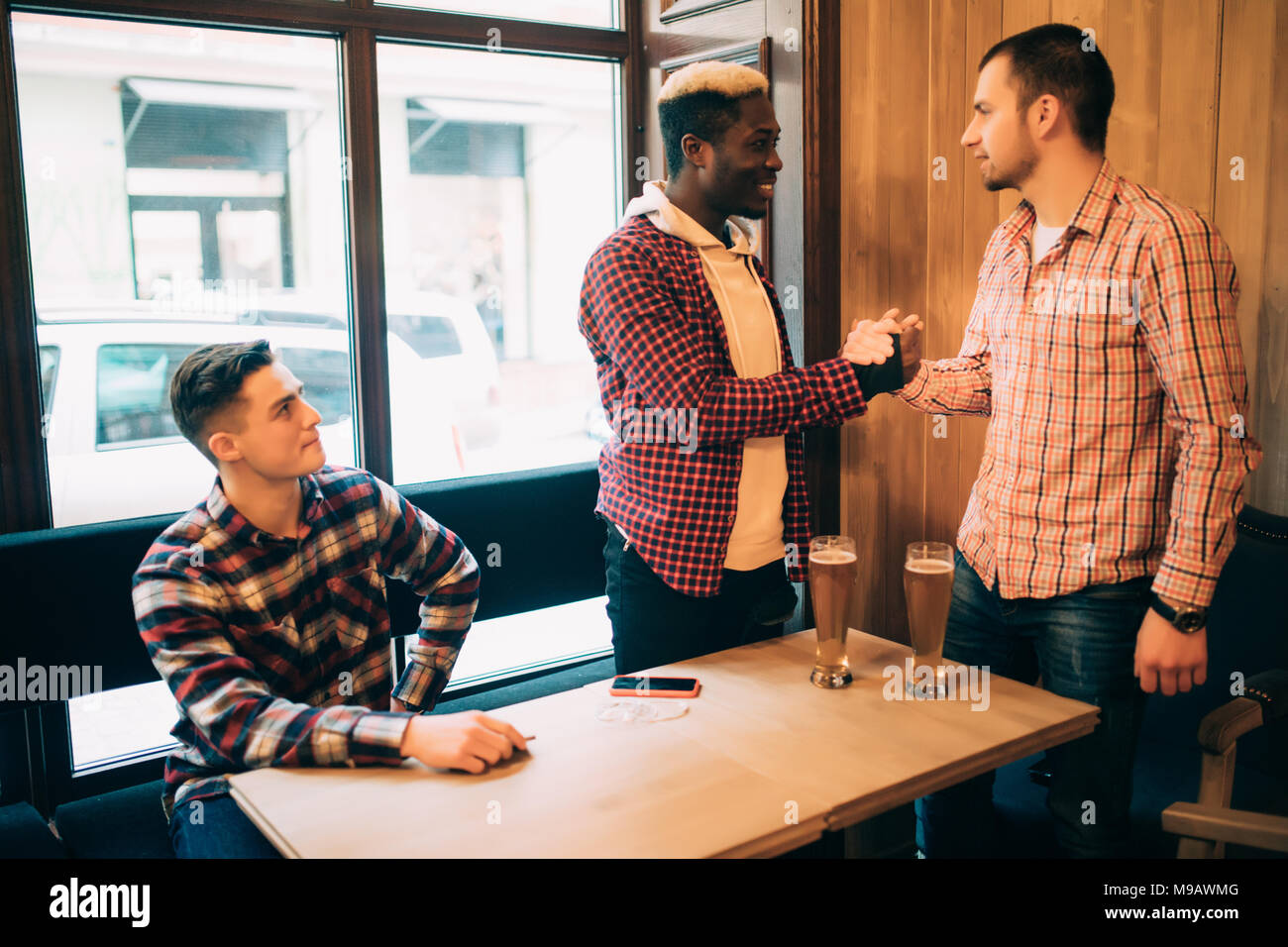Happy to finally meet old male friends in bar. Shaking hands and smiling. - Stock Image