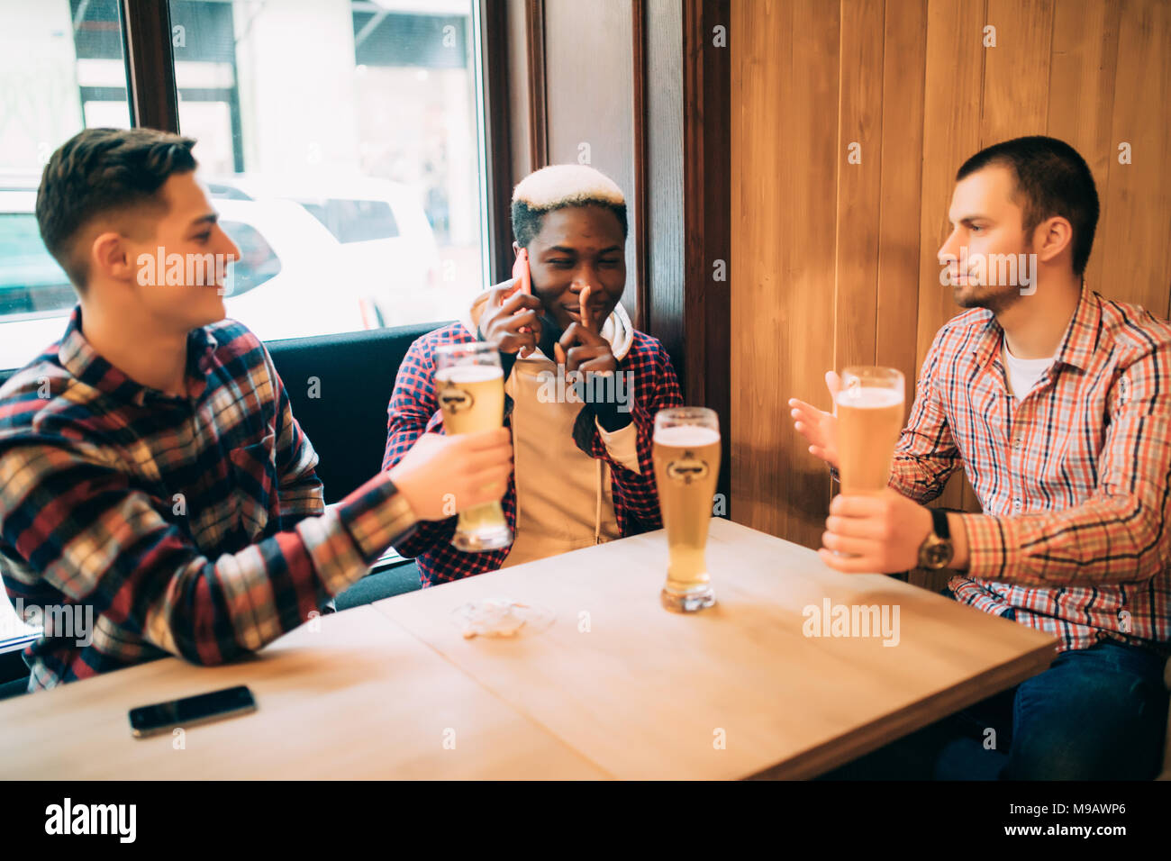 Two male friends in bar are drinking beer and communicating while one is talking on phone and asking for silence. - Stock Image